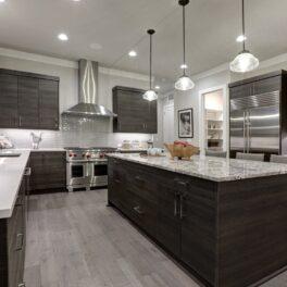 Bucătărie modernă, cu accesorii argintii. Podeaua e gri, mobilierul e maro închis și blatul e alb cu picățele. Tehnologia din imagine e una dintre numeroasele invenții NASA