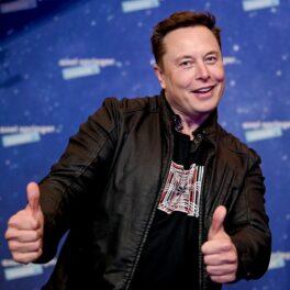 Elon Musk pe covorul roșu al Premiilor Axel Springer, decembrie 2020. Poartă un tricou negru, cu o geacă neagră de piele, cu fundal albastru