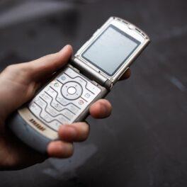 Motorola Rarz V3 pe argintiu, în mâna unui utilizator, cu fundal gri spre negru. Motorola Razr V3 e un telefon flip. E unul dintre cele mai vândute telefoane mobile din istorie