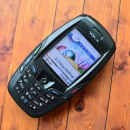 Telefon mobil Nokia 6600 în culoare neagră, pe un fundal de lemn maro, cu ecranul deschis. Se numără printre cele mai vândute telefoane mobile din istorie