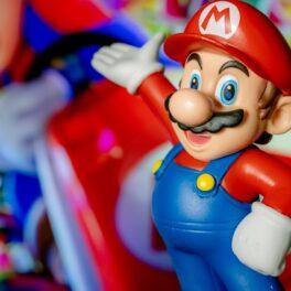 Personajul Mario, pe un fundal în ceață cu obiecte Mario. Figurina poartă salopetă albastră, bluză și șapcă roșii. Există multe detalii secrete din Super Mario Bros