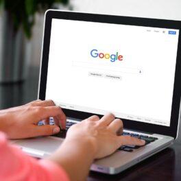 Laptop deschis, cu Google pe ecran. Mâinile utilizatorului sunt pe tastatură, e îmbrăcat în roz. Tastatura e gri. Motorul de căutare include 7 trucuri Google pe care trebuie să le știi