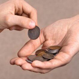 Schimb de monede între două mâini, pe fundal bej. Monedele sunt argintii, aurii și roșii. Experții au vorbit despre prima profesie din lume