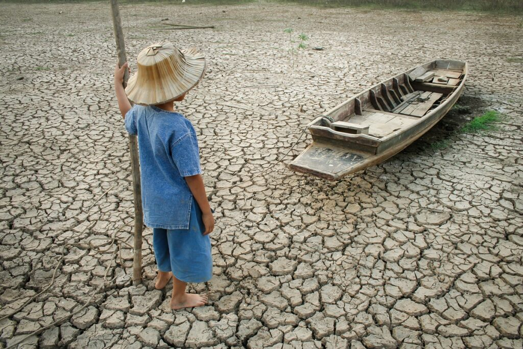 Băiat ccare se află pe un teren arid, crăpat, lângă o barcă. El e îmbrăcat în albastru