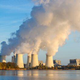 Emisii de dioxid de carbon din turnuri albe, pe malul lacului, cu cerul albastru pe fundal