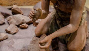 Imagine cu om din neanderthal care încearcă să facă focul. poartă blonuri și are pietre in mână