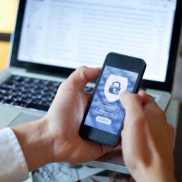 Bărbat care ține smartphone în mână cu ecran albastru. În față are un laptop deschis. Are un simbol de securitate, ca atunci când vrei să te asiguri că cineva îți urmărește telefonul