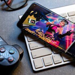 Garena Free Fire pe ecranul unui telefon Android, negru, care stă pe o tastatură albă. E un joystick negru lângă. Se numără printre cele mai descărcate jocuri Android