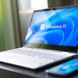 laptop cu windows 11 pe ecran. Tastatură gri, stă pe masă lângă un telefon. Ambele ecrane sunt albastre. Microsoft va lansa Windows 11 la finalul acestui an