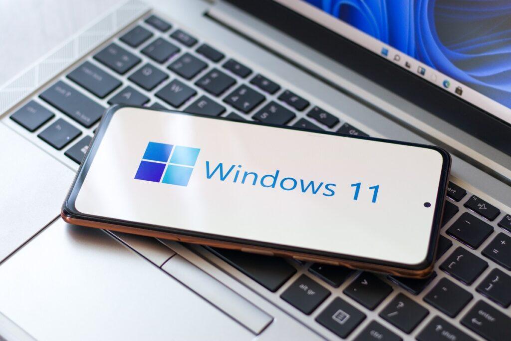 Telefon cu Windows 11 pe ecran. Ecranul e alb, cu simbolul Windows 11. Telefonul e pe o tastatură gri cu negru