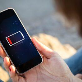 Cineva ține un telefon cu baterie descărcată în mână. Ecranul e negru. Listă cu locurile în care nu trebuie să îți încarci telefonul vreodată