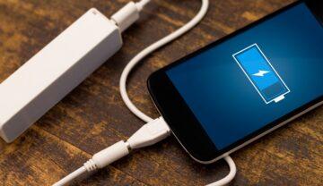 Telefon negru cu ecran albastru care e la încărcat cu o sursă albă, pe o masă de lemn închis. Mulți s-au întrebat ce se întâmlă dacă lași telefonul la încărcat toată noaptea