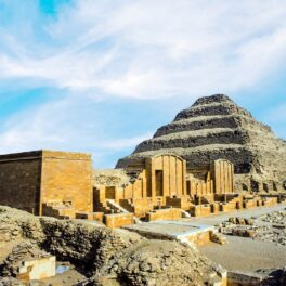 Piramida lui Djoser, una dintre cele mai vechi piramide din lume, fotografiată ziua. Tsructurile de la baza ei sunt galbene, piramida e bej, fundal cu cer albastru