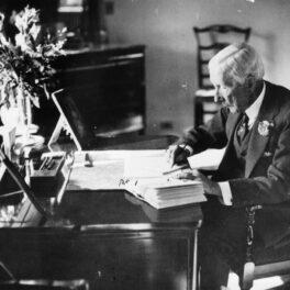 John D. Rockefeller stă în scaun, la birou, și scrie. E îmbrăcat în costum. Fotografie alb-negru. El a devenit primul miliardar din istoria SUA