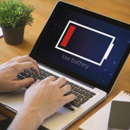 Laptop pe birou de lemn, cu mâinile utilizatorului pe taste. Are o baterie pe ecran care se scurge. Dacă te gândești cum să îți încarci laptopul fără să afectezi bateria, trebuie să urmezi câteva reguli simple