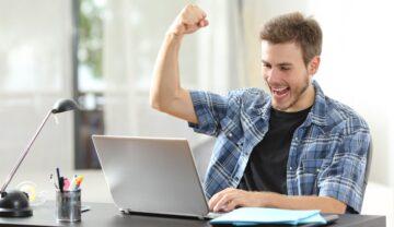 Bărbat în fața unui laptop, joacă jocuri video, mâna în sus. Laptopul e gri. Experții au analizat cum pot schimba jocurile video comportamentul jucătorilor