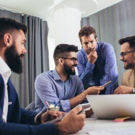 Imagine cu 4 bărbați, care vorbesc în jurul mesei. Sunt îmbrăcați în costume și cămăși, se uită peste o foaie. Se înțeleg pentru că limbile umane au gramatică similară