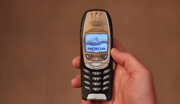 Telefon Nokia 6310 original, pe negru, ținut în mână, cu un fundal bej. Noua variantă Nokia 6310 a fost lansată în anul 2021