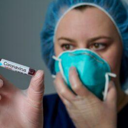 Cercetătorii au descoperit o epidemie de coronavirus care a afectat Asia de Est în urmă cu 20.000 de ani. În imagine e o doctoriță, cu masca pe față, care ține o fiolă de coronavirus în mână