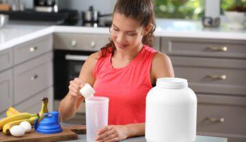 Femeie care stă în bucătărie și își prepară shake de proteine, pe fundal gri. Provocarea virală de pe Tiktok include pudra de proteine pre-antrenamet