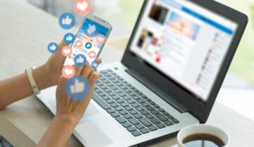 Femeie care folosește rețelele de socializare. Stă la un birou bej, cu un laptop deschis în față și un telefon în mână, cu like-uri. Experții susțin că rețelele de socializare ar putea deveni un pericol
