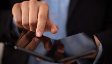 Bărbat care folosește un telefon pliabil, negru, similar cu Samsung W22 5G dezvăluit recent. Poartă un costum negru și o cămașă albastră