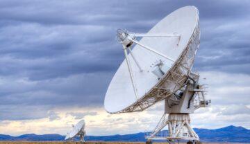 Antenă cu satelit mare, de culoare albă, în centrul câmpului, cu cer înnorat pe fundal. Un telescop ce a ajutat la detectarea Semnalele radio misterioase din Calea Lactee avea 36 de antene cu satelit