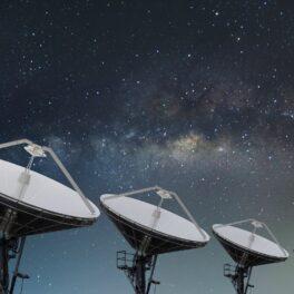 Cercetatorii cred că au aflat ce cauzează semnalul misterios din Calea Lactee. În imagine sunt trei radare mari, albe, cu cerul cu calea lactee pe fundal