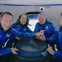 William Shatner și echipajul navetei Blue Origin care a ajuns în spațiu în octombrie 2021. Sunt toți îmbrăcați în costume albastre, stau la masă și se țin de mână