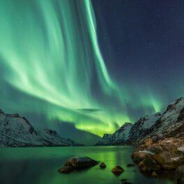 Aurora Boreală deasupra apei, cu munți în partea dreaptă, are culoare verde-albastra. Aurora Boreală va fi vizibilă în teritorii mai sudice decât de obicei