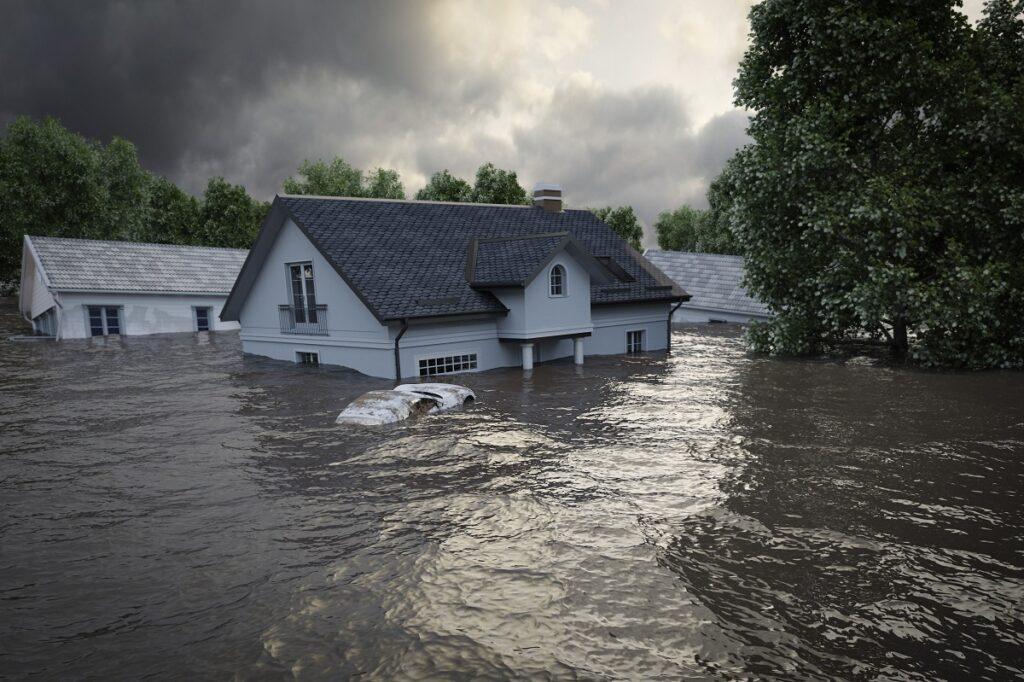 Inundație gravă într-o zonă rezidențială. Apa ajunge până deasupra ferestrelor casei albe, cu acoperiș gri