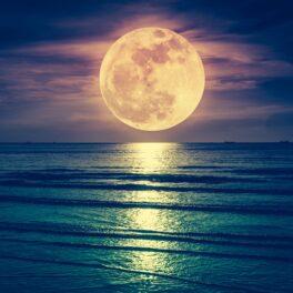 Luna deasupra mării, noaptea. Apa e albastră, Luna e galbenă și se reflectă în suprafață