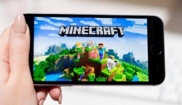 Ecran Minecraft pe telefon negru, ținut în mână de o femeie, pe fundal alb. Mulți jucători s-au întrebat cum poți găsi structuri în Minecraft