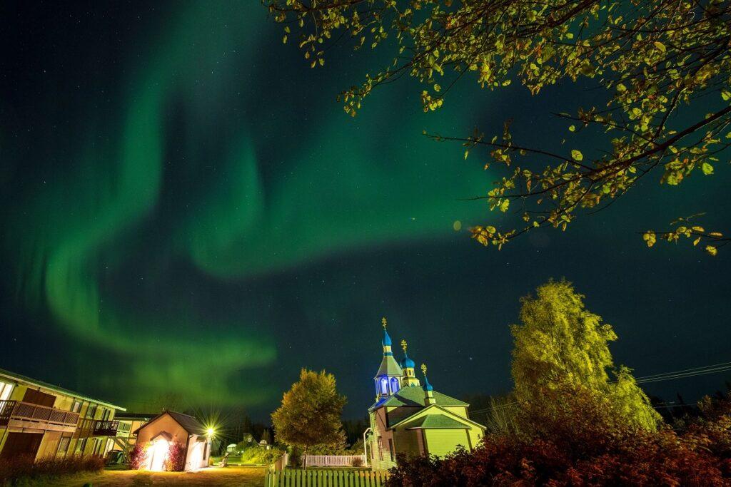 Aurora Boreală va fi vizibilă mai la sud din cauza unei furtuni geomagnetice. Se văd pe cer verde, cu oraș dedesubt
