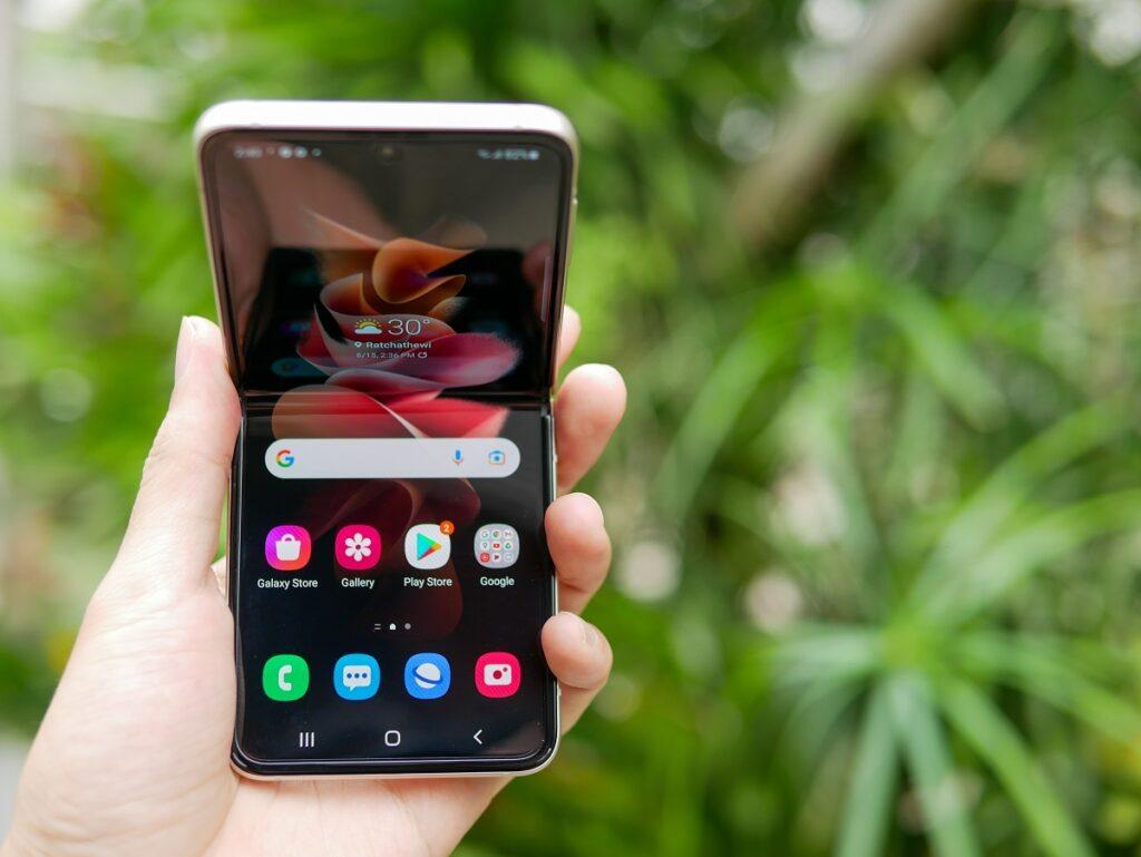Telefon Galaxy Z Flip 3 Samsung ținut în mână, deschis, cu fundal cu frunze verzi