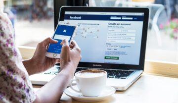 Imagine cu o utilizatoare care folosește Facebook pe laptop și pe telefon. Stă la birou și are laptopul deschis și are un telefon în mână. Unele trucuri Facebook nu sunt cunoscute nici de către utilizatorii vechi